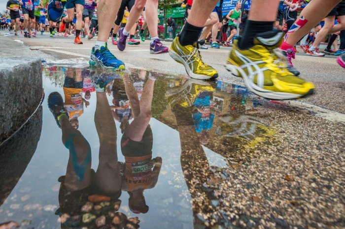 close up of runners trainers at the London Marathon 2015 and reflection of runners in puddle